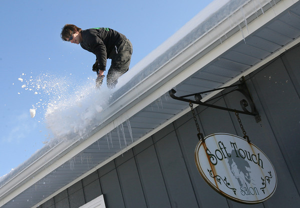 Gloucester: Adrian Dinapoli of Family Tree Company removes snow from the roof of Soft Touch Salon as a precautionary measure due to the weight of the snow and ice. Photo by Kate Glass/Gloucester Daily Times