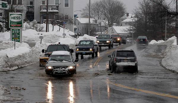 Gloucester: Cars slow down before passing through a flooded section of Main Street yesterday. Snow covered many storm drains making it difficult for the rain to drain. Photo by Kate Glass/Gloucester Daily Times