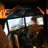 Gloucester: Firefighters Marc Nicastro and Bob Rivas watch as Charles Scola  participates in a driving safety simulator program outside Central Station yesterday. The simulator, which is presented by the Massachusetts Interlocal Insurance Association, is designed to reduce the risk of accidents and lower the city's insurance costs. Photo by Kate Glass/Gloucester Daily Times