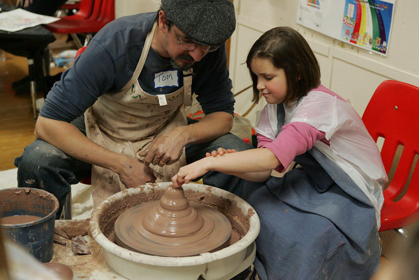 Essex: Eliza Woodward, 7, learns how to throw clay from Tom Duff during Messy Art night At Essex Elementary School. Mary Muckenhoupt/Gloucester Daily Times