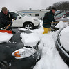Gloucester: Mike Moore and Don Sudbay remove snow from nearly 160 cars in the lot at Sudbay Family Automotive Center yesterday. Sudbay says tomorrow's cleanup will be worse because they will have to chisel all the ice off the cars. Photo by Kate Glass/Gloucester Daily Times