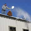 Gloucester: Bob Charland thorws snow off the roof of the Bomco building on Gloucester Avenue alongside Mark Chaisson and Dave Warner, right, after Bomco employees were let out on a half day as a safety precaution Friday afternoon. Mary Muckenhoupt