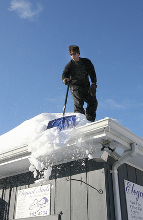 Gloucester: Adrian Dinapoli of Family Tree Company removes snow from the roof of Elegant Nails as a precautionary measure due to the weight of the snow and ice. Photo by Kate Glass/Gloucester Daily Times