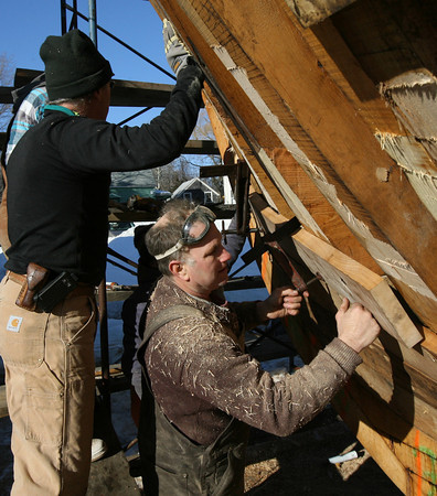 Essex: Harold Burnham, Pierre Erhard, Bruce Slifer, and Steve Willard secure the plank with clamps. Photo by Kate Glass/Gloucester Daily Times