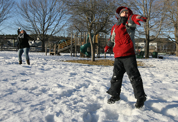 Manchester: Julian Friend and his caretaker, Nina Harbecka, try to see how far they can throw snowballs at Masconomo Park yesterday afternoon. They were aiming at different trees and then the roof of the band stand. Photo by Kate Glass/Gloucester Daily Times