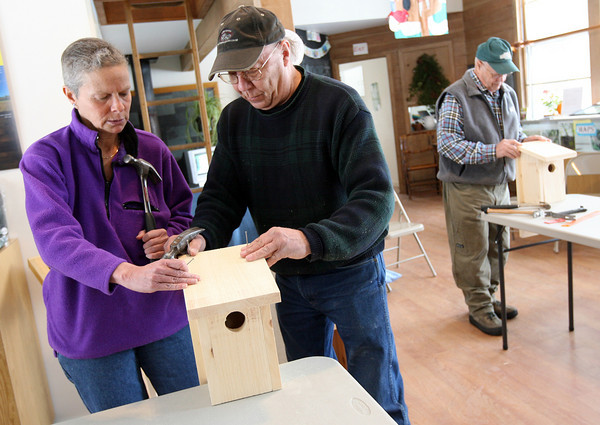 Gloucester: Ed Jylkka helps Karen Cooper nail down the roof of her Eastern bluebird birdhouse at the Cape Ann Discovery Center at Ravenswood Park yesterday. Jylkka says the birdhouses will attract the bluebirds because of the size of the opening, the depth of the house, and their location, which will be near open meadows approximately five feet off the ground. Photo by Kate Glass/Gloucester Daily Times