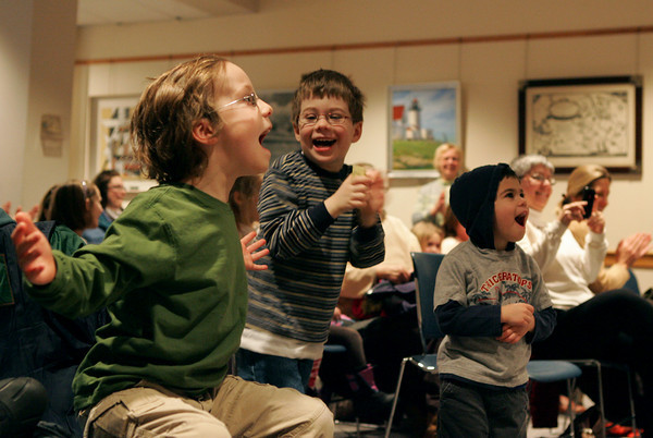 Rockport: From left, Eli Mueler, Damien Sorrenti and Andrew Sorrenti clap and cheer for Danno Sullivan the ukulele man at the Rockport Public Library Saturday morning.  Sullivan was playing a tiny harmonica with no hands when the crowd started to cheer. Mary Muckenhoupt/Gloucester Daily Times