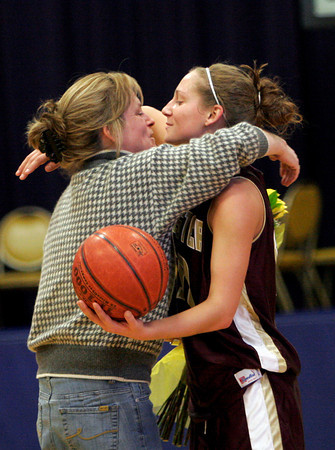Lynn: Holly Cain gives her daughter, Hannah Cain, a bouquet of flowers and a hug after Hannah scored her 1,000th career point during Gloucester's game against Tewksbury at St. Mary's High School in Lynn yesterday. Photo by Kate Glass/Gloucester Daily Times
