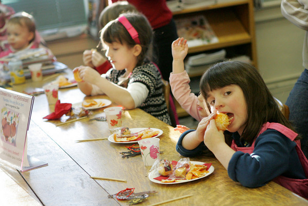 Essex: Parker Hollingsworth, 7, bites into her tangerine like she's biting into an apple while enjoying her snack at the Chinese New years Party at the TOHP Burnham Library Thursday afternoon. The party included stories and a fun dragon craft as well. Mary Muckenhoupt/Gloucester Daily Times