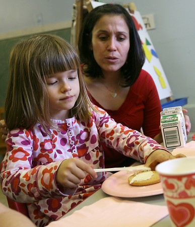Gloucester: Marni Frithsen helps Lotus Marshall decorate a cookie for Valentines Day at Gloucester Preschool at Fuller School yesterday. Photo by Kate Glass/Gloucester Daily Times
