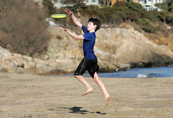 Manchester:  Tyler Malik, 11, jumps up to catch a Frisbee while playing with his dad at Singing Beach Wednesday afternoon.  Tyler didn't seem to mind the cold, except at one point when he ran into the water to retrieve the Frisbee. Mary Muckenhoupt/Gloucester Daily Times