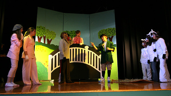 """Essex: Justin Figurido as the wolf and Larson Tolo as the troll decide on a plan while surrounded by the three little pigs, Holly Fossa, Elizabeth Hull, and Kayley Wright, and the three billy goats gruff, Nell McKeon, Courtney Doane, and Savannah Reilly, while rehearsing for Essex Elementary School's production of """"The Surprising Story of the Three Little Pigs,"""" which runs tonight and tomorrow at 6:30. Photo by Kate Glass/Gloucester Daily Times"""