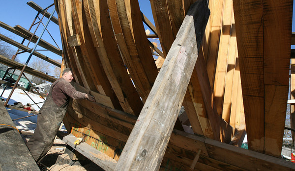 Essex: Harold Burnham presses a board against the schooner Ardelle to make sure the edges are sanded properly before attaching the plank. Photo by Kate Glass/Gloucester Daily Times