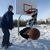 Essex: Azzie Economo, 12, reaches for the ball after his friend, Stephen Friend, 13, dunks behind Essex Elementary School on Sunday. Because the snow is piled up so high behind the school, the hoops are much easier to reach. Photo by Kate Glass/Gloucester Daily Times