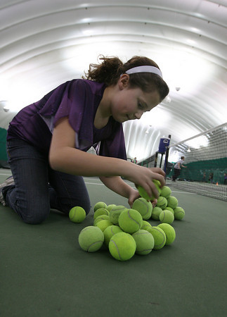 Ashley Stanton, a student at Plum Cove Elementary School, concentrates as she tries to stack a group of tennis balls during the Enrichment Program at the Manchester Athletic Club on Tuesday. Students would race from the other end of the tennis court with a ball for their team's pile and try to carefully balance the balls on top of each other. Photo by Kate Glass/Gloucester Daily Times