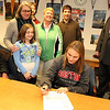 ALLEGRA BOVERMAN/Staff photo. Gloucester Daily Times. Gloucester: Clare Pleuler, seated at center, signed her letter of intent to play soccer at Boston University next year on Wednesday. Around her are, from left: her father, Dave Pleuler, mother Eileen Murphy, sister Maeve Pleuler, 10, brother Devin Pleuler, 23, Athletic Director Kim Patience, Matthew Duncan of the Guidance office and Principal William Goodwin.