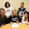 ALLEGRA BOVERMAN/Staff photo. Gloucester Daily Times. Manchester: Manchester-Essex field hockey player Taylor Coons, seated at center, was signing her letter of intent to attend Saint Anselm College to play field <br /> hockey on Wednesday. Around her from left are her father, Loren Coons,  <br /> athletic director, Kelly Porcaro, Assistant Principal Paul F. Murphy, and varsity field hockey coach Andrea Slaven.