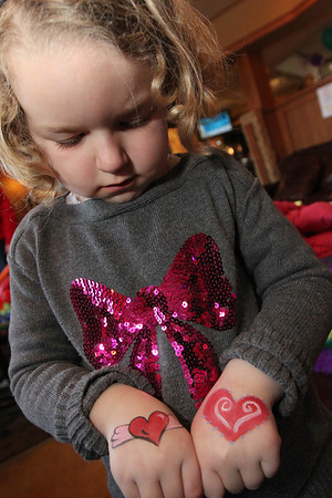ALLEGRA BOVERMAN/Staff photo. Gloucester Daily Times. Gloucester: Maeve Coletti, 4, of Swampscott, shows off her painted hands. She, her sister and grandmother were participating during Mardi Gras festivities and the Cape Ann YMCA's full day fundraiser at Latitude 43. The fundraiser is for Y teens and chaperones to travel to and volunteer in New Orleans during April school vacation and help rebuilt homes destroyed by Hurricanes Katrina and Rita.