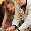 Scientist Michael Bergen shows first-grader Paige Garlitz what her experiment will look like the next day: jelly marbles. This was part of an interactive science program sponsored by Top Secret Science on Monday morning. Jesse Poole/Gloucester Daily Times Jan. 30, 2011
