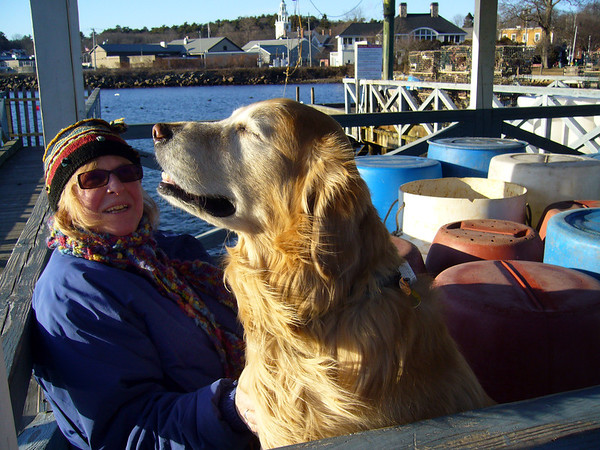 ALLEGRA BOVERMAN/Staff photo. Gloucester Daily Times. Manchester: Anna Kasabian of Manchester sits  in a pavilion at the town docks with her golden retriever Amos, 6, on Monday afternoon at about 4 p.m. Every day since he was a puppy, between 3:30 and 4 p.m., Amos likes to have her walk him to this very spot and he sits on the bench there and turns his face into the sun and wind just like this. This is their special time they spend together and it's vital for them both.