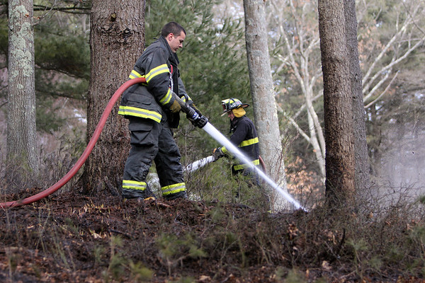 ALLEGRA BOVERMAN/Staff photo. Essex: Essex firefighters put out three separate brush fires that grew from controlled burns at 32 Haskell Court in Essex on Tuesday. FIrefighters David Barrett is at left, Edward Neal behind him at right.