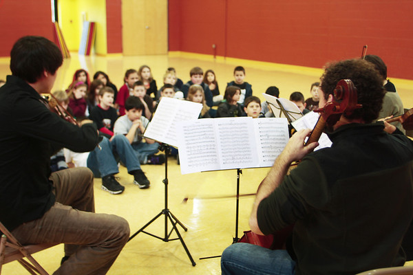 Frank Shaw, left, plays the viola as Michael Unterman, right, plays the chello, and two other members of A Far Cry perform in front of a group of elementary students at the Gloucester Community Arts Charter School, where they also educated the students about classical music on Wednesday morning. The group performed at the Shalin Liu Performance Center in Rockport on Wednesday evening.  Jesse Poole/Gloucester Daily Times Feb. 29, 2012