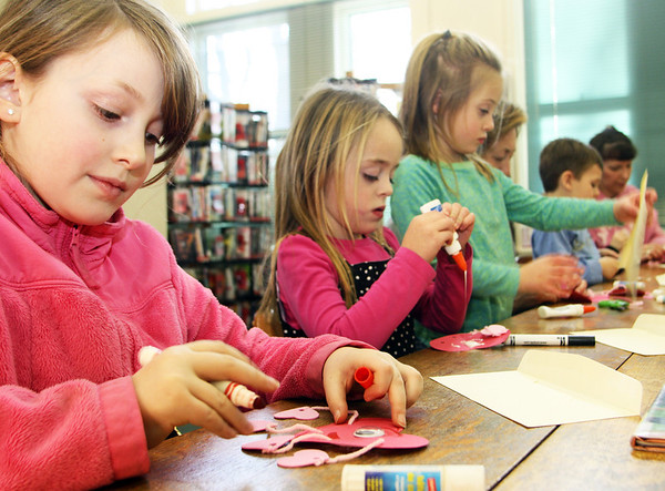 From left, Alanna Fitzgerald, 9, draws a face on her Valentine's Day project, as Ava Fritsch, 5, pours a good amount of glue on her project to secure the eye, while her twin, Aubrey, looks at her artwork from afar. This was part of a Valentine's Day art event at the T.O.P.H. Burnham Library in Essex on Monday afternoon. Jesse Poole/Gloucester Daily Times Feb. 13, 2012