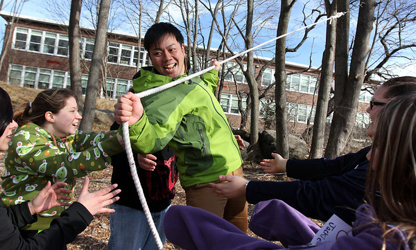 "ALLEGRA BOVERMAN/Staff photo. Gloucester Daily Times. Gloucester: <br /> <br /> In a ""tension traverse"" exercise, Andy Shogo center, tries to carefully make his way on a low hanging rope as others stand ready to catch him if he were to fall. Around him from left are: Sabrina Thompson, Miranda Schneider, Dylan Spellman, Kayla Collibee and Jaclyn Canillas.  Project Adventure of Gloucester High School and Project Adventure of Japan convened at the high school on Wednesday for activities."