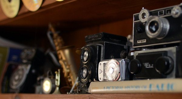 Photo Courtesy of Jake Levin/Gloucester Daily Times. Details of Roger Wonson's collection of old cameras on display in the recording studio in his home in Beverly.