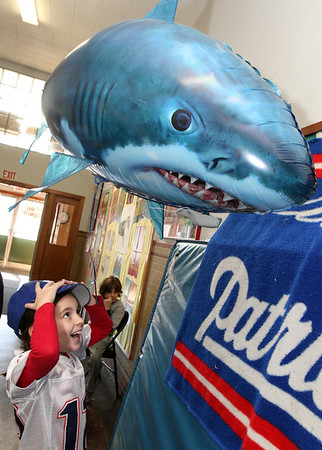 "ALLEGRA BOVERMAN/Staff photo. Gloucester Daily Times. Gloucester: East Gloucester Elementary second grader Kayla Calomo reacts to the remote controlled antics of a ""shark blimp,"" that is being operated by one of her classmates with the help of two Gloucester High School students, David St. Peter and James Cavanaugh, during a daylong visit to the school by Gloucester High School Honors Physics and Physics of Robotics classes students on Friday. The blimp, while not built by students, helps demonstrate buoyancy and explain the mechanical devices it's comprised of."
