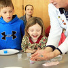 First-graders Patrick Cronin and Katherine Prinn of Manchester Memorial Elementary School peek into Michael Bergen's hands to see the future of one of their experiments: jelly marbles. This was part of an interactive science program put on by Top Secret Science on Monday morning. Jesse Poole/Gloucester Daily Times Jan. 30, 2011
