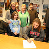 ALLEGRA BOVERMAN/Staff photo. Gloucester Daily Times. Gloucester: <br /> Clare Pleuler, seated at center, signed her letter of intent to play soccer at Boston University next year on Wednesday. Around her are, from left: her father, Dave Pleuler, mother Eileen Murphy, sister Maeve Pleuler, 10, brother Devin Pleuler, 23, Athletic Director Kim Patience, Matthew Duncan of the Guidance office and Principal William Goodwin.