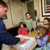 ALLEGRA BOVERMAN/Staff photo. Gloucester Daily Times. Gloucester:The Coast Guard Cutter Grand Isle returned to Gloucester on Friday afternoon after seven months of repairs and 10 days at sea. Petty Officer Christopher Cahill of Newmarket, N.H., left, cuts cake in the ship's mess for the Hoffman family children of Beverly, center back, Meagyn, 2, and Jordyn, 7, and the Gaudio family of Rockport, right, including mom Valarie, front right, and next to her: Evelyn, 6, Christjan II, 3, and Isabella, 8.