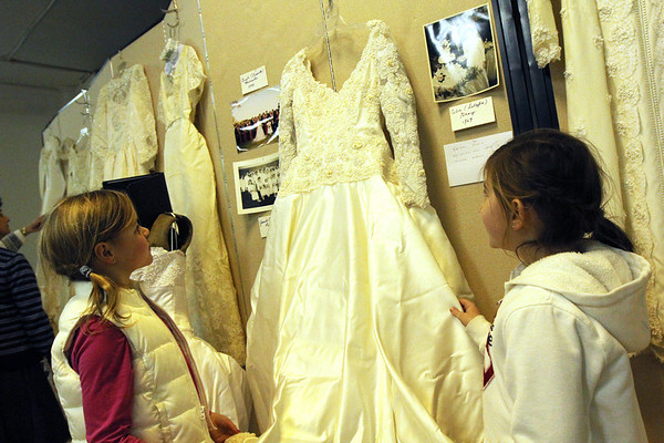 "ALLEGRA BOVERMAN/Staff photo. Gloucester Daily Times. Gloucester: From left: Alli Smith, 9, and her best friend Lauren Movalli, 8, both of Gloucester, examine the wedding dress worn by Movalli's mother, Gayle Lucido Movalli at the  Women's Guild of Holy Family Parish held a ""Romance""- themed evening on Tuesday night at St. Ann Church."