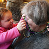 ALLEGRA BOVERMAN/Staff photo. Gloucester Daily Times. Gloucester: Brynn Coletti, 2, of Swampscott, left, plays Mardi Gras beads worn by her grandmother Cathy Meany of Rockport on Tuesday. They were participating during Mardi Gras festivities and the Cape Ann YMCA's full day fundraiser at Latitude 43. The fundraiser is for Y teens and chaperones to travel to and volunteer in New Orleans during April school vacation and help rebuilt homes destroyed by Hurricanes Katrina and Rita.