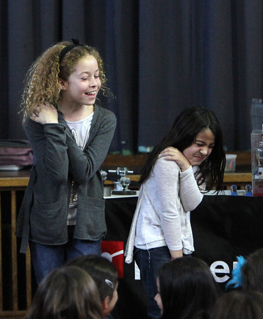 ALLEGRA BOVERMAN/Staff photo. Gloucester Daily Times. Gloucester: During a PTO-sponsored enrichment program at Beeman Elementary School on Friday given by the Museum of Science. Museum educator George Pechmann who had one hand on a van de Graaf Generator, was demonstrating that humans conduct electricity. While he touched the hand of one student, the others behind him also got shocked because they each had a hand on one another's shoulder. Reacting to the shock are, from left, Hope Miller and Bianca Soares.