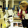 "ALLEGRA BOVERMAN/Staff photo. Gloucester Daily Times. Gloucester: From left: The Women's Guild of Holy Family Parish held a ""Romance""- themed evening on Tuesday night at St. Ann Church. Members brought three generations of wedding dresses to display, wedding photos and wedding album, cake toppers, bridesmaid and mother-of-the-bride dresses and other memorabilia. There was a candy table, cupcakes on every table, and champagne, too. Meg Fennessey Smith, who was married in 2001, looks at wedding photos and albums."