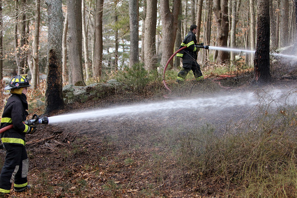 ALLEGRA BOVERMAN/Staff photo. Essex: Essex firefighters put out three separate brush fires that grew from controlled burns at 32 Haskell Court in Essex on Tuesday. FIrefighters Edward Neal is at left, David Barrett is at upper right.
