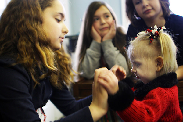 Jesse Poole/Staff photo. Gloucester Daily Times. Gloucester: Third-grader Anabelle Palumbo, left, holds hands with McKenna Ciolino, 2, who is diagnosed with Emanuel syndrome, a rare chromosome abnormality. Her mother, Chelsie Larry of Gloucester, brought McKenna to Eastern Point Day School on Tuesday morning in order to help educate students on the specific syndrome.
