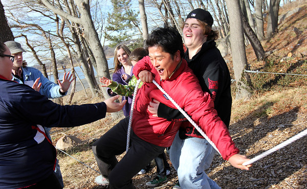 """ALLEGRA BOVERMAN/Staff photo. Gloucester Daily Times. Gloucester: In a """"tension traverse"""" exercise, Takashi Monden, center, almost falls as he tries to carefully make his way on a low hanging rope as others stand ready to catch him if he were to fall. At far right, catching his fall, is Dylan Spellman, at far right is Kayla Collibee, and second from left is Nick Saulnier, Jaclyn Canillas and Miranda Schneider. Project Adventure of Gloucester High School and Project Adventure of Japan convened at the high school on Wednesday for activities."""