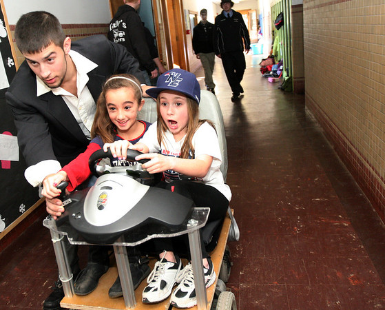"ALLEGRA BOVERMAN/Staff photo. Gloucester Daily Times. Gloucester: During a daylong visit to East Gloucester Elementary school by Gloucester High School Honors Physics and Physics of Robotics classes students on Friday. From left: GHS senior Kyle Lucido, left, guides second graders Gabriella Lapa, middle, and Kaitlyn Jackson, down the hall aboard a ""wheelchair go-cart"" designed by senior Brian Lapoint, not shown. Lapoint said that the device has an X-box controller for the steering wheel and a wheelchair battery. He built the hybrid device just ""as a cool thing. It has a steering wheel where it normally doesn't."""