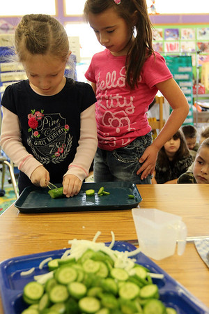 "ALLEGRA BOVERMAN/Staff photo.Gloucester Daily Times. Gloucester: FoodCorps and CitySprouts hosted ""Pickle Pioneer"" day at Veterans Memorial Elementary School on Thursday. The kindergarten class taught by Janet Allen actually made pickles out of cucumbers and onions, sugar, vinegar and salt. Students each helped slice cucumbers, including, from left: Molly Pennimpede and Kajsa Curcuru."