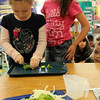 """ALLEGRA BOVERMAN/Staff photo.Gloucester Daily Times. Gloucester: FoodCorps and CitySprouts hosted """"Pickle Pioneer"""" day at Veterans Memorial Elementary School on Thursday. The kindergarten class taught by Janet Allen actually made pickles out of cucumbers and onions, sugar, vinegar and salt. Students each helped slice cucumbers, including, from left: Molly Pennimpede and Kajsa Curcuru."""