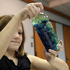 ALLEGRA BOVERMAN/Staff photo. Gloucester Daily Times. Gloucester: Kaci Orlando, 7, makes waves inside a water bottle by tilting it, after creating a lava lamp-like effect with water, oil, food coloring and Alka Seltzer tablets, during the monthly science workshop at the Sawyer Free Library on Tuesday. More tablets can be added to create more fizz to the mixture on an ongoing basis to keep up the effect. Children were learning about the density of liquids and solids.