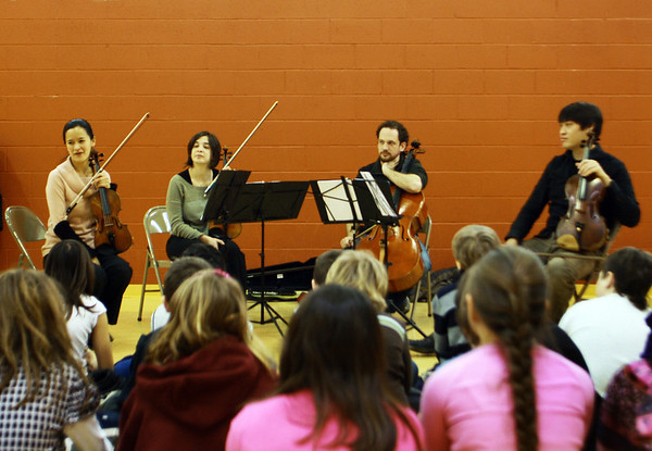 From left, Megumi Stohs, Sharon Cohen, Michael Unterman and Frank Shaw, all members of A Far Cry, visit the Gloucester Community Arts Charter School on Wednesday morning to perform before a group of elementary students, where they also educated the students about classical music. The group performed at the Shalin Liu Performance Center in Rockport on Wednesday evening. Jesse Poole/Gloucester Daily Times Feb. 29, 2012
