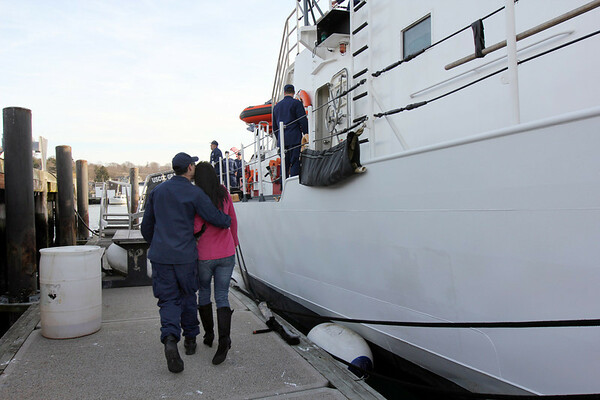 ALLEGRA BOVERMAN/Staff photo. Gloucester Daily Times. Gloucester:The Coast Guard Cutter Grand Isle returned to Gloucester on Friday afternoon after seven months of repairs and 10 days at sea. Thomas Ciarametaro, left, hugs his fiancee Sabre Thompson, both of Gloucester, as they board the ship.
