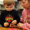 Zachary Welch, 3, of Gloucester, works on a Valentine's Day project with his mom, Neva, at the T.O.P.H. Burnham Library in Essex on Monday afternoon. Jesse Poole/Gloucester Daily Times Feb. 13, 2012