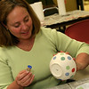 ALLEGRA BOVERMAN/Staff photo. Gloucester Daily Times. Gloucester: Lauren Gudonis of Manchester uses the end of a cork to make almost perfect dots on the bowl she was decorating during the decorating night held at The Open Door Tuesday evening in preparation for the upcoming Empty Bowl Dinner on Thurs., May 10 from 4-8 p.m. at Cruiseport Gloucester. A second session for decorating will be held on Sat. Mar. 10 from 10 a.m. - noon at 28 Emerson Ave. in Gloucester. For more information, see foodpantry.org or call 978-283-6776, extension 205.