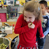 """ALLEGRA BOVERMAN/Staff photo.Gloucester Daily Times. Gloucester: FoodCorps and CitySprouts hosted """"Pickle Pioneer"""" day at Veterans Memorial Elementary School on Thursday. The kindergarten class taught by Janet Allen actually made pickles out of cucumbers and onions. Sampling them, from front to back are: Brigitte Lawson, Wilson Ortiz and Abigail Doucette. Brigitte wasn't sure she liked the taste."""