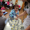 "ALLEGRA BOVERMAN/Staff photo.Gloucester Daily Times. Gloucester: FoodCorps and CitySprouts hosted ""Pickle Pioneer"" day at Veterans Memorial Elementary School on Thursday. They served different kinds of pickles at lunch and kids had to vote on their favorites among daikon radishes and cucumbers. Grace Cherubino, right, a FoodCorps service member, offers samples to second graders Jhailenny Tejada, left, and Kayllany Costa."